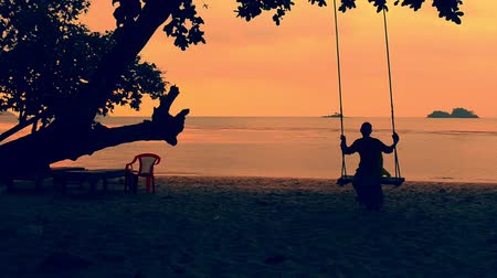 ленивый : Silhouette of beautiful girl relaxing on a swing at the beach Стоковые видеозаписи