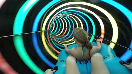 akció : Slope down by water slide in water park. Fun travel inside of the multi color tube at aqua park filmed on action camera. Slow motion.
