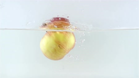 underwater shot : Slow Motion Video of Apple Falling in Water with Spalsh Stock Footage