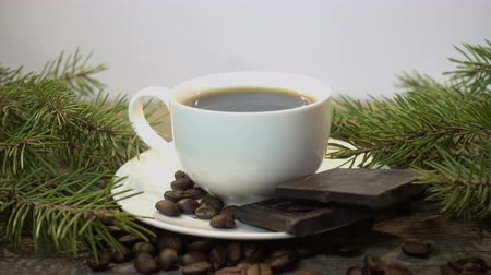 vagens : 4K view of a cup of coffee with spruce branches, coffee beans and a piece of chocolate.