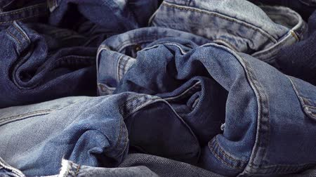 western wear : A pile of trendy blue jeans pants on a wooden background. HD video clip