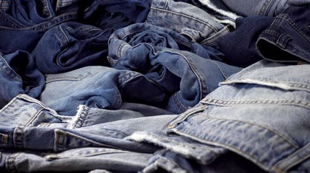 western wear : A pile of trendy blue jeans pants on a wooden background. Stock Footage