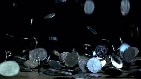 srebro : Slow motion, a pile of coins falling on a wooden table on a black background. Ukrainian coins in denomination of five kopecks are falling into a heap