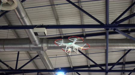 uav : 4K view of demonstration flight of a drone or quadrocopter inside the building