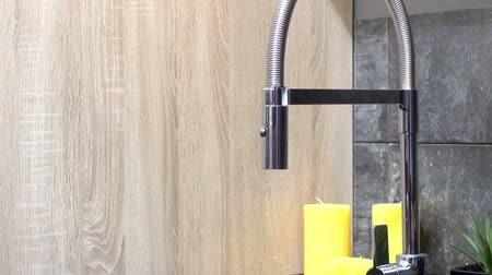 csőhálózat : Modern kitchen faucet and yellow candles on the kitchen countertop. HD video