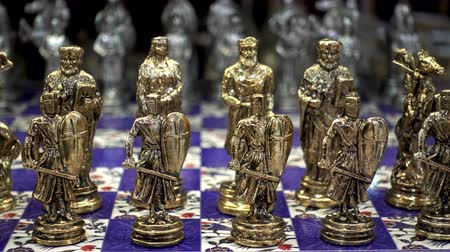 lovagi torna : 4K view of the golden chess pieces in the shape of the ancient soldiers close-up. Stock mozgókép