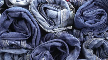 western wear : Pile of rolled up jeans as background. HD video Stock Footage