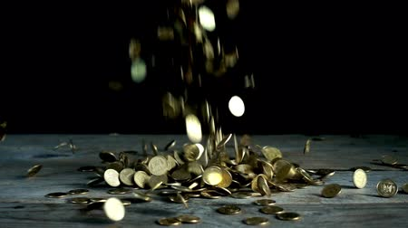 rakás : Slow motion, a pile of coins falling on a wooden table on a black background. Ukrainian pennies are falling a heap Stock mozgókép