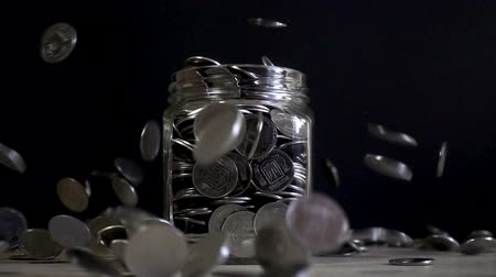 экономить : Slow motion, a pile of coins falling into an empty glass jar on a black background. Ukrainian coins fall into a jar.