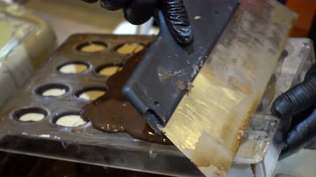 pralina : 4K view of professional confectioner pours melted chocolate into plastic molds. Chocolate candy making. Vídeos