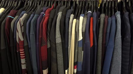 knitted : Fashionable collection of warm clothes. Various sweaters hang on hangers on the rack. HD video Stock Footage