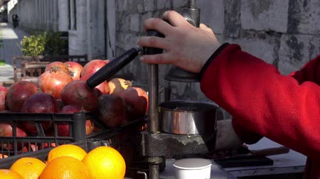 Squeezing the juice from fresh pomegranate fruit. Sale and production of fruit juices by hand press. HD video