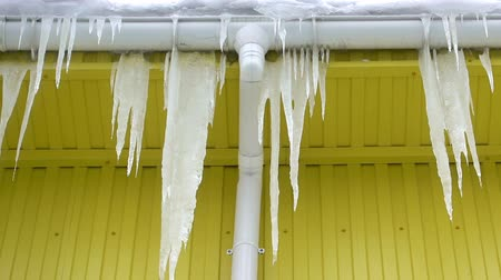 Large dangerous icicles hang on a frozen roof. HD video
