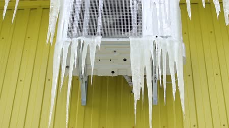 Frozen air conditioner in ice icicles on a yellow wall. HD video