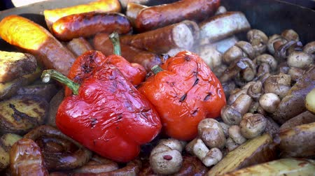 4K view of various vegetables and mushrooms grilled. Appetizing red pepper close-up. Street food.
