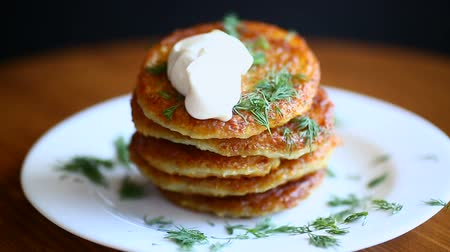 оладья : potato pancakes with dill in a plate
