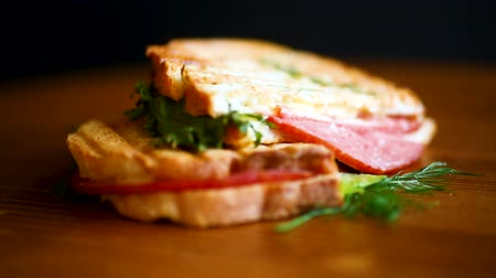 crostini : sandwich with fresh salad and greens and sausage on a wooden table