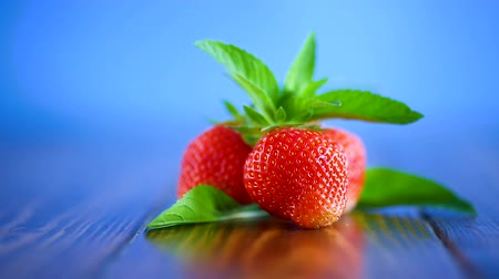 ovocný : ripe red organic strawberry on a blue background