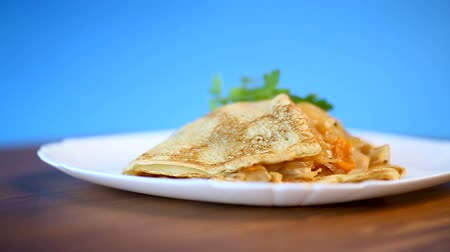 креп : thin fried pancakes stuffed with stewed cabbage in a plate
