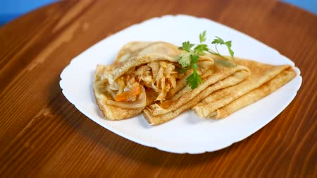 nalesniki : thin fried pancakes stuffed with stewed cabbage in a plate