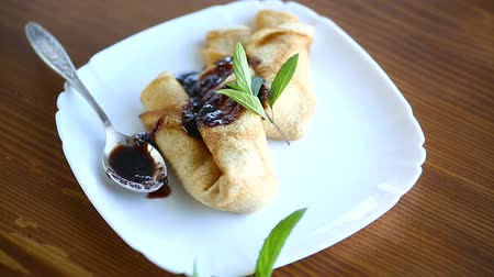 креп : thin fried pancakes stuffed with jam in a plate