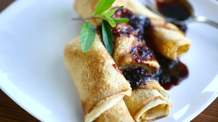 dut : thin fried pancakes stuffed with jam in a plate on a wooden table Stok Video