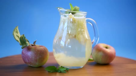glass pitcher : summer sweet cold compote of fresh apples with a sprig of mint in a glass decanter