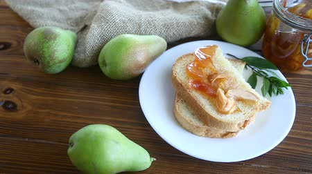 pears : pieces of bread with sweet home-made fruit jam from pears and apples in a plate on a wooden table