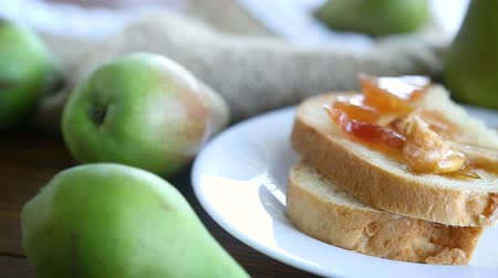 grzanki : pieces of bread with sweet home-made fruit jam from pears and apples in a plate on a wooden table