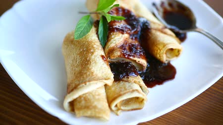креп : thin fried pancakes stuffed with jam in a plate on a wooden table Стоковые видеозаписи