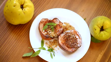 pigwa : sweet ripe quince baked with walnuts and honey on a wooden table
