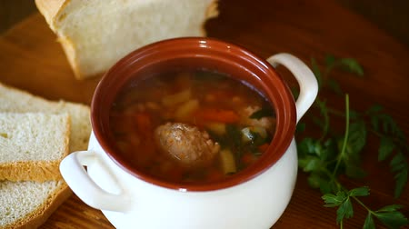 rosół : vegetable soup with beans and meatballs in a ceramic bowl