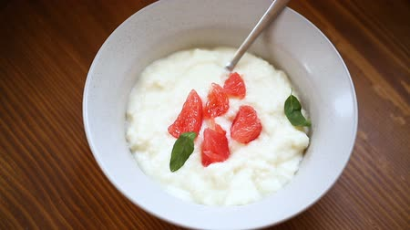 búzadara : sweet boiled semolina porridge in a plate with slices of red grapefruit