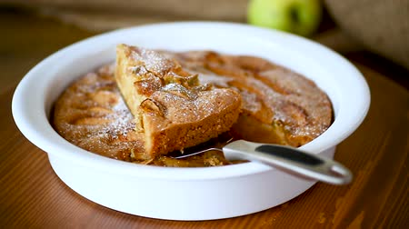 charlotte pie : sweet apple pie in ceramic form on a wooden Stock Footage