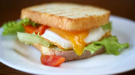 желток : fresh sandwich with lettuce leaves and fried egg with hot toasts Стоковые видеозаписи