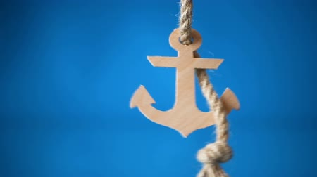 джут : wooden decorative anchor on a blue background