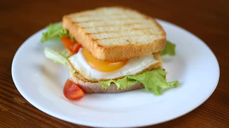 poached egg : fresh sandwich with lettuce leaves and fried egg with hot toasts Stock Footage