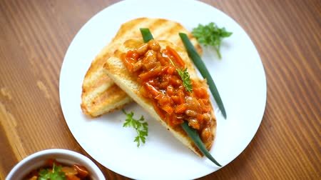 chili paprika : fried bread toasts with stewed beans and vegetables in a plate