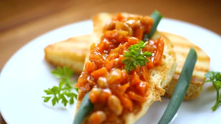 карри : fried bread toasts with stewed beans and vegetables in a plate