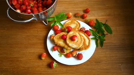 оладья : fried sweet pancakes with ripe strawberries in a plate Стоковые видеозаписи