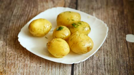 houten bord : boiled young potato with butter and dill in a plate Stockvideo
