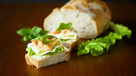 twaróg : sandwich with cheese, salad leaves and red fish on a wooden