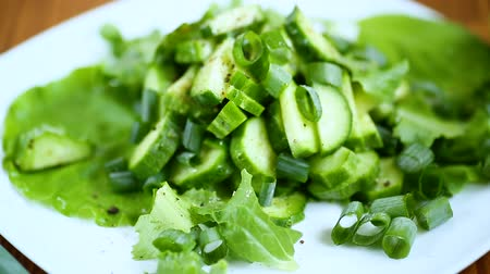 ovoce a zelenina : fresh salad of cucumbers and greens in a plate on a wooden