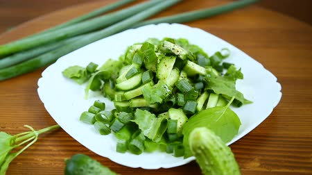 bowls : fresh salad of cucumbers and greens in a plate on a wooden