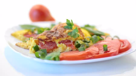 fried omelet from homemade organic eggs with tomatoes and green onions