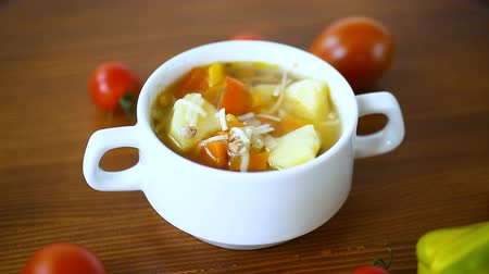 суп : vegetable soup with noodles, tomatoes, peppers and other vegetables in a plate Стоковые видеозаписи