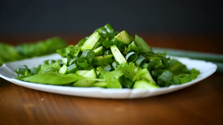 white onion : fresh salad of cucumbers and greens in a plate on a wooden
