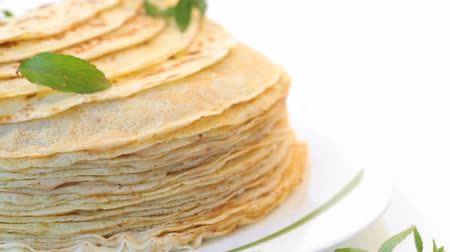 креп : many fried thin pancakes in a plate, on white background.