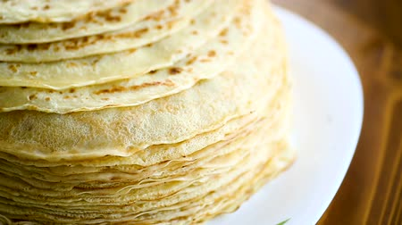 креп : many fried thin pancakes in a plate, on a table.