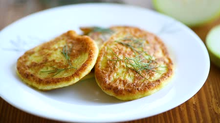 оладья : vegetable fritters made from green zucchini in a plate